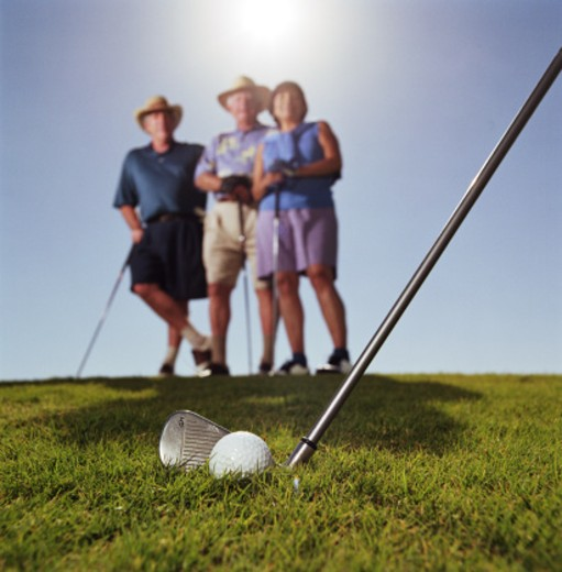 Stock Photo: 1527R-1150178 Three mature golfers waiting on fairway, focus on golf club and ball