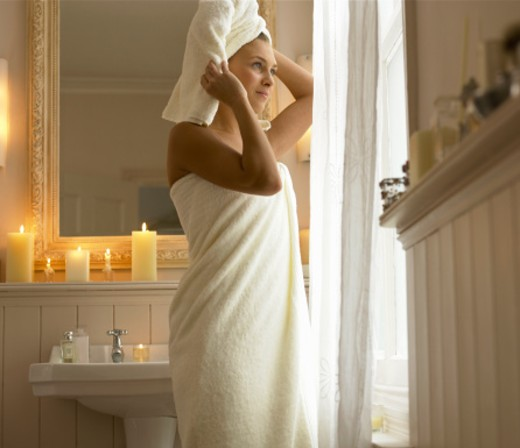 Young woman wearing bathtowel in bathroom : Stock Photo