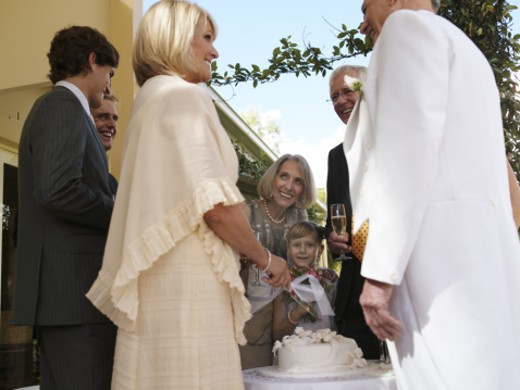 Bride cutting wedding cake, groom and guests smiling, low angle view : Stock Photo