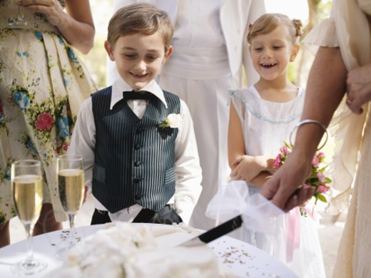 Pageboy and flowergirl (6-7)watching wedding cake being sliced : Stock Photo