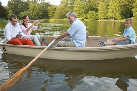 Three generational family in rowing boat, grandfather rowing : Stock Photo