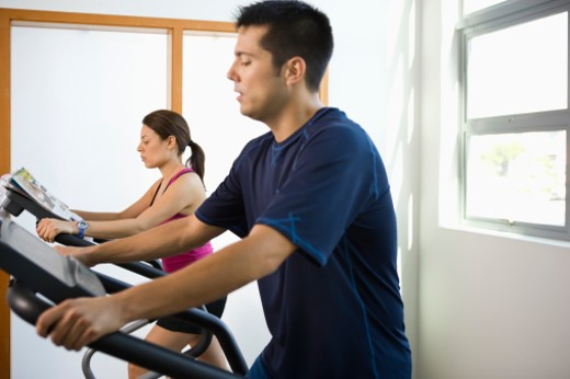 Young couple working out on elliptical machines in gym : Stock Photo