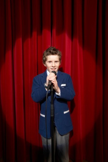 Spotlight on on boy (11-13) holding microphone on stage, portrait : Stock Photo