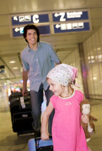Stock Photo: 1527R-1152346 Father and daughter (2-4) walking in airport