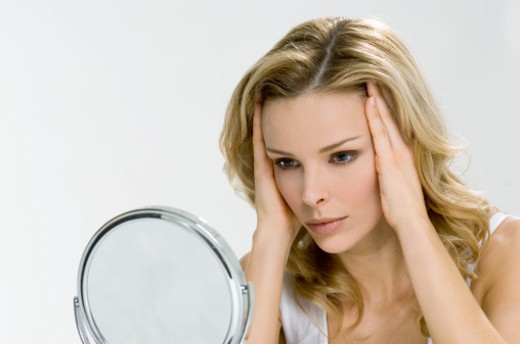 Stock Photo: 1527R-1152886 Young woman looking in mirror, hands on face, close-up