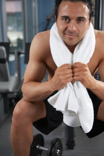 Young man with towel around neck sitting on weight bench, portrait : Stock Photo