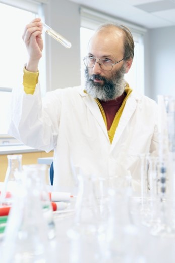 Mature man examining liquid in test tube in laboratory : Stock Photo