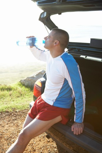 Stock Photo: 1527R-1154025 Man in sportswear on the open boot of car drinking bottled water