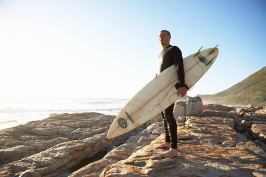 Man in wetsuit with surfboard on rocks : Stock Photo