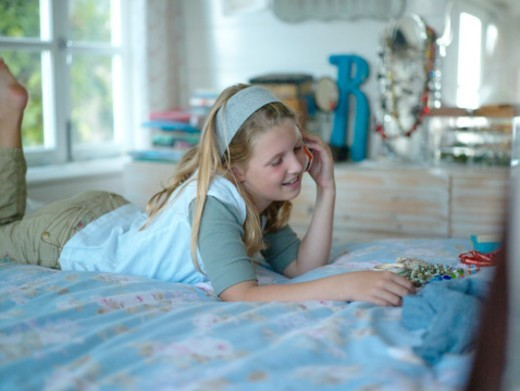 Stock Photo: 1527R-1155505 Girl (8-10) using on phone on bed