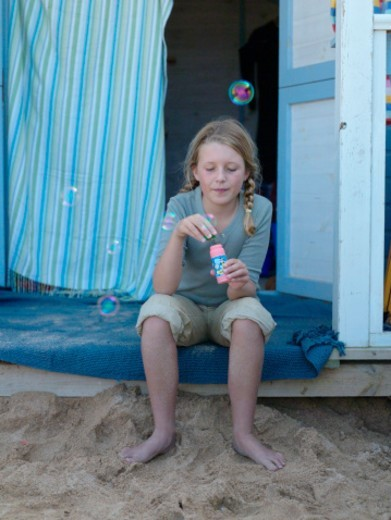 Girl (8-10) making soap bubbles on porch : Stock Photo