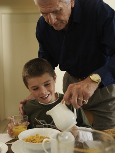 Stock Photo: 1527R-1155712 Senior man pouring milk from jug into grandson's (8-9) bowl of cereal