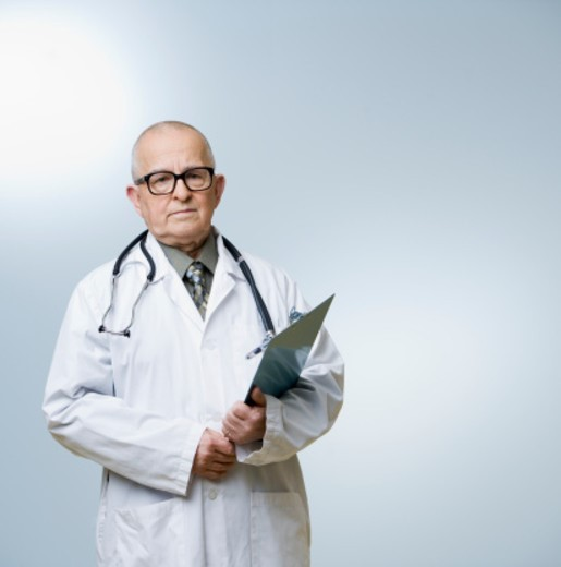 Senior male doctor holding clipboard, portrait : Stock Photo