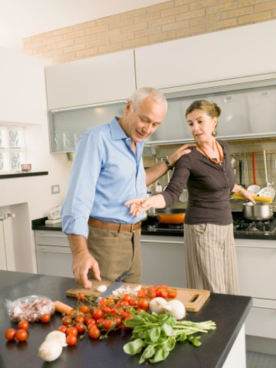 Mature couple cooking together in kitchen : Stock Photo
