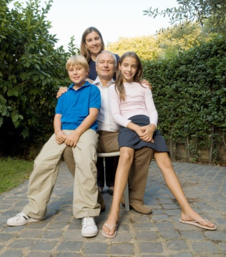 Grandparents with grandchildren (8-12) in garden, smiling, portrait : Stock Photo