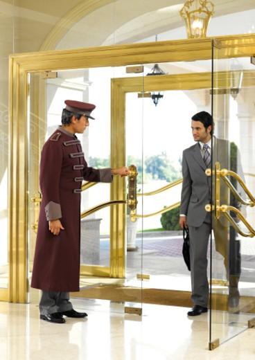 Stock Photo: 1527R-1157563 Concierge holding door open for businessman