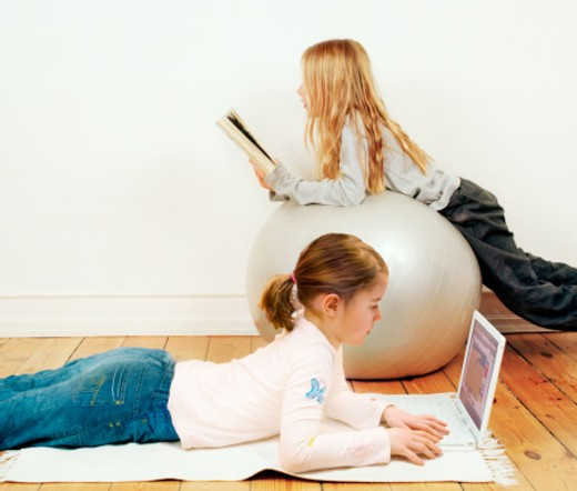 Stock Photo: 1527R-1157721 Two girls (7-9) relaxing in living room, reading and looking at laptop