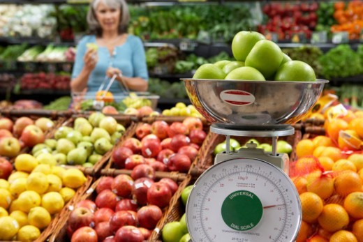 'Mature woman in supermarket, focus on weighing scale' : Stock Photo