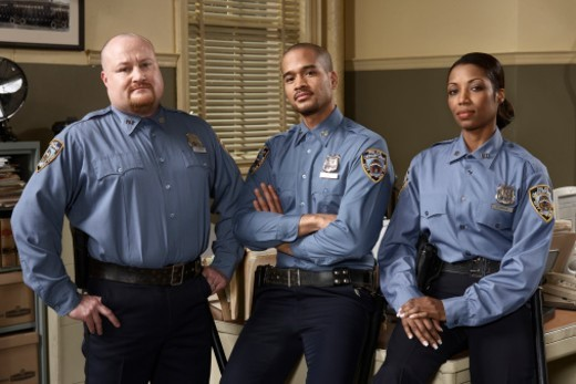 Three police officers in office, portrait : Stock Photo
