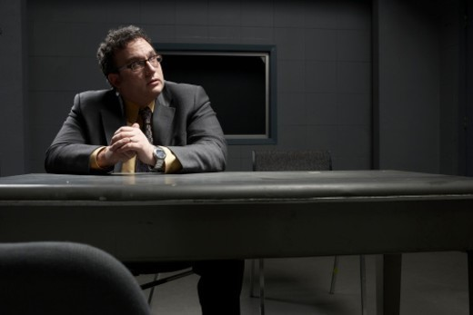 Man sitting at desk in interrogation room, looking away : Stock Photo