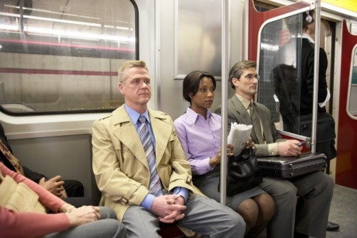 People in subway train, sitting side by side : Stock Photo