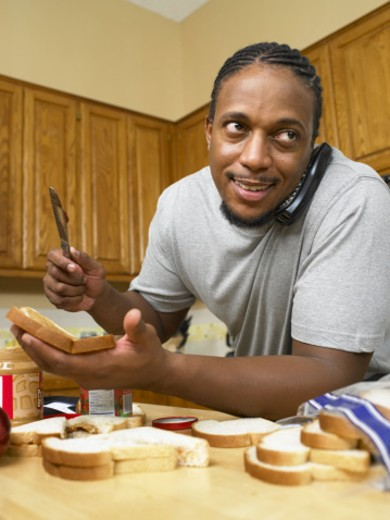 Man making sandwiches listening to telephone : Stock Photo