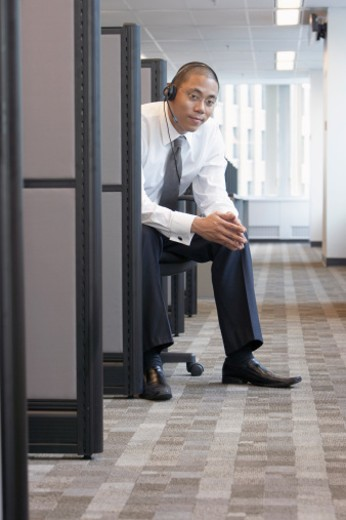 Stock Photo: 1527R-1159315 Office worker sitting, wearing headset, in row of cubicles