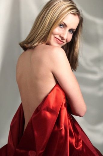 a young caucasian blonde wrapped in red satin sheet exposing her back turns around and smiles : Stock Photo