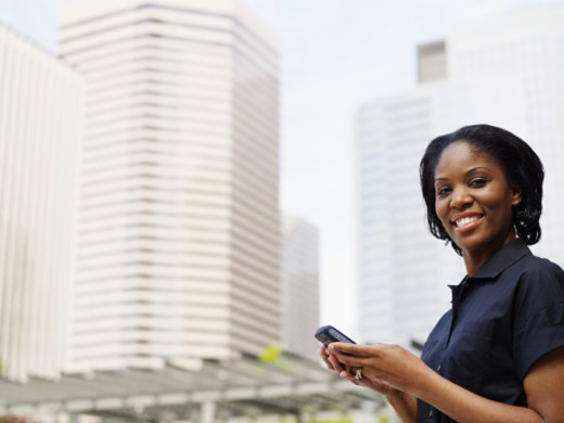 Businesswoman holding PDA and smiling : Stock Photo