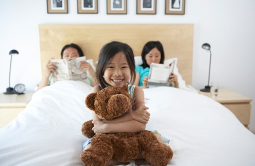 Girl (6-7) holding teddy, sitting on parents' bed, portrait : Stock Photo