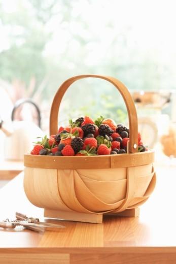 Basket of fresh raspberries and blackberries on kitchen counter : Stock Photo