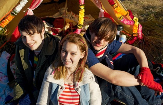 Portrait of teenage girl (16-17), teenage boy (14-15) and young man sitting outside tent, smiling, high angle view : Stock Photo