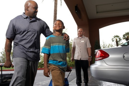Father and son (6-7 years) walking with suitcases through hotel driveway, low angle view : Stock Photo
