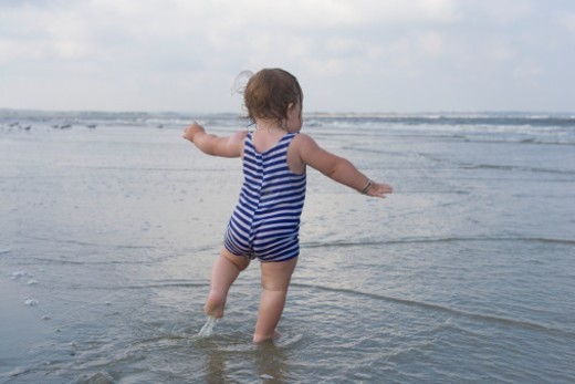 Baby girl (9-12 months) on beach, rear view : Stock Photo