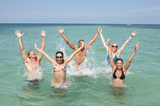 Stock Photo: 1527R-1164547 Friends having fun in sea, laughing with arms raised
