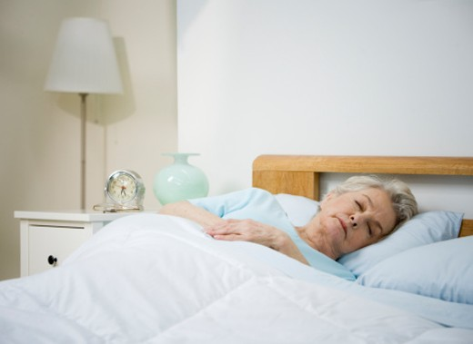 Senior woman sleeping in bed at home : Stock Photo
