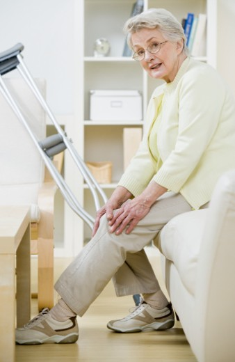 Stock Photo: 1527R-1165145 Senior woman sitting on sofa with crutches, holding knee, portrait