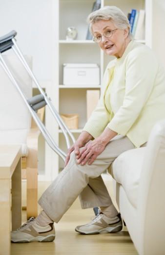 Senior woman sitting on sofa with crutches, holding knee, portrait : Stock Photo