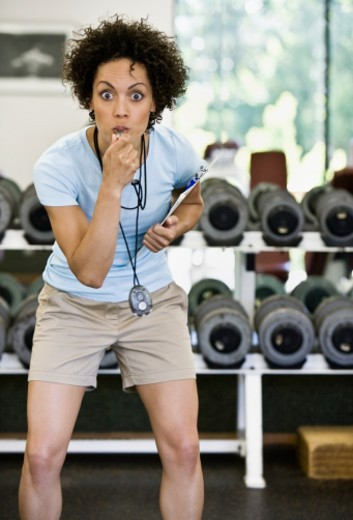 Female trainer blowing whistle in gym, portrait : Stock Photo