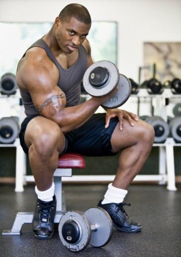 Stock Photo: 1527R-1165234 Man weight training in gym, portrait