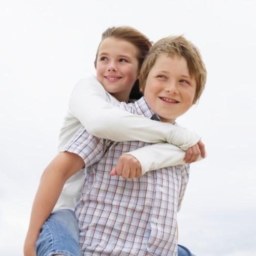 Stock Photo: 1527R-1165351 Boy (12-13) giving girl (10-11) piggy back outdoors