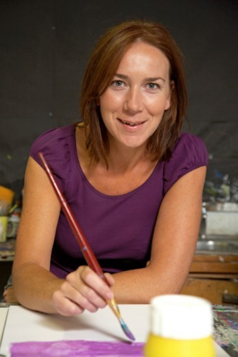 Woman in art classroom, painting, smiling, portrait : Stock Photo