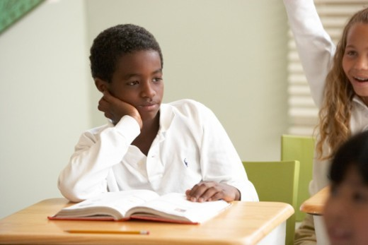 Boy (9-11) sitting at desk in classroom : Stock Photo