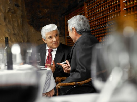 Two senior businessmen talking in restaurant, view across table : Stock Photo