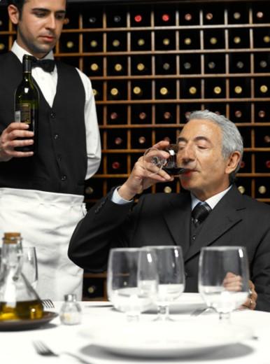 Stock Photo: 1527R-1166481 Senior businessman tasting wine, waiter holding bottle