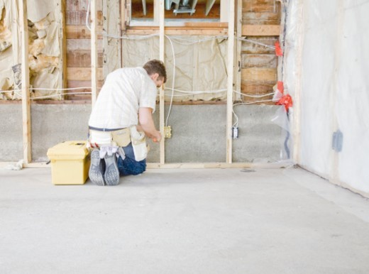 Stock Photo: 1527R-1167015 Man working on electricity in house under construction, rear view