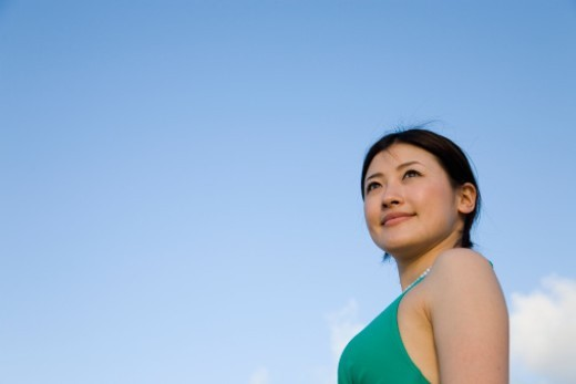 Young woman standing under blue sky, low angle view, portrait : Stock Photo