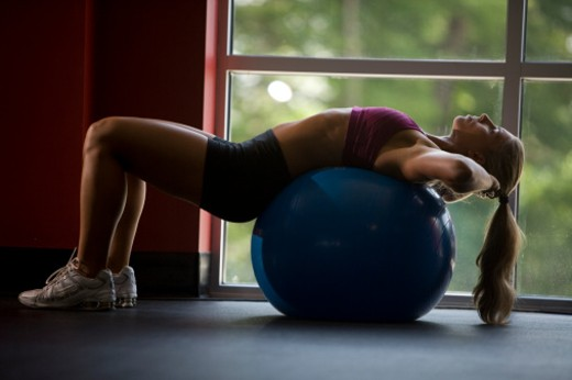 Young woman bending over backwards on exercise ball, side view : Stock Photo