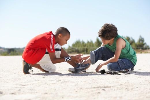 Two boys (9-11) squatting on sand, tying shoelaces : Stock Photo