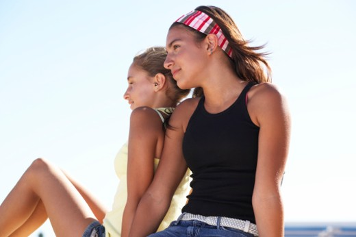 Stock Photo: 1527R-1167805 Two girls (12-14) sitting outdoors, low angle view